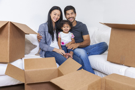 Asian Chinese family, parents and young girl child daughter, packing or unpacking boxes and moving into a new home.