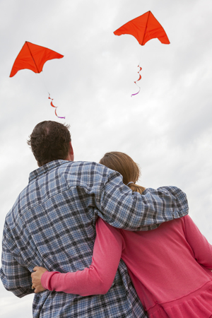 divergence: Relationship troubles concept photograph of man & woman couple flying a red kite each in different directions Stock Photo