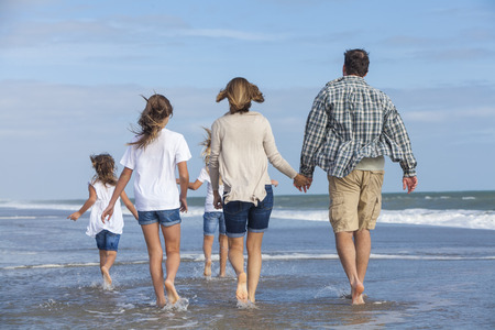 Rear view of family mother, father, daughter, parents and female girl children walking in the sea on a beach  photo