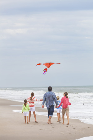 Happy family mother, father, daughter, parents and female girl children flying a red kite, playing & laughing on a beach