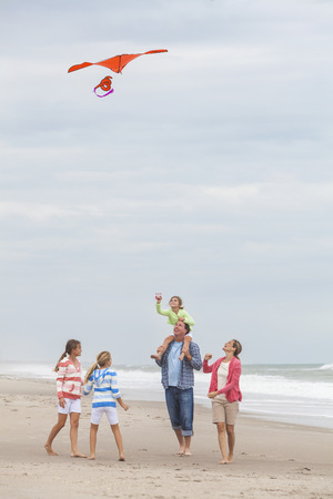 flying kite: Happy family mother, father, daughter, parents and female girl children flying a red kite, playing & laughing on a beach