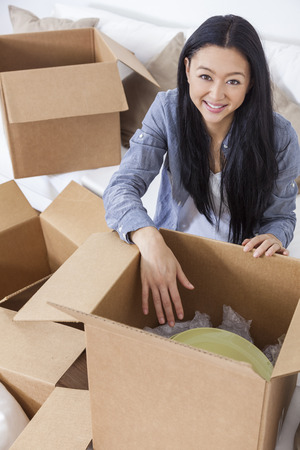 unpacking: Asian Chinese girl or young woman packing or unpacking boxes and moving into a new home.