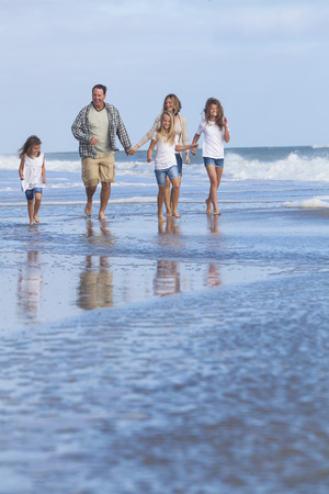 Family mother, father, daughter, parents and female girl children walking in the sea on a beach  photo