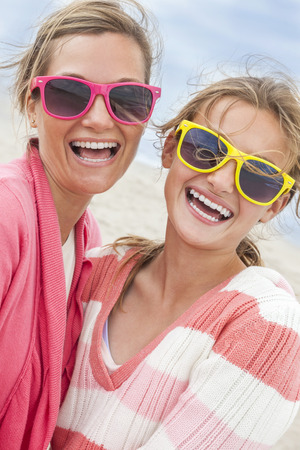 Mother & daughter, woman female girl child having fun wearing sunglasses & taking selfie photograph on a beach photo