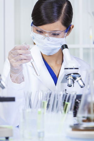 A Chinese Asian female medical or scientific researcher or doctor with test tube & using a microscope in a laboratory photo