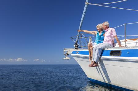 Een gelukkige senior paar zittend op de zijkant van een zeilboot op een kalme blauwe zee kijken en wijst naar een duidelijke horizon