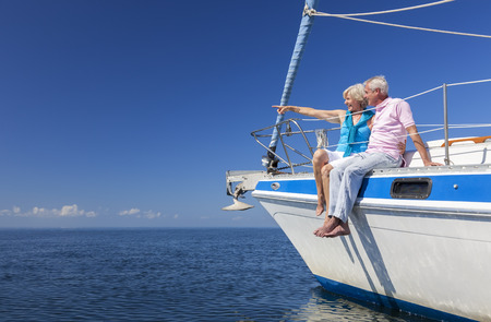 donna ricca: Una coppia felice anziano seduto sul lato di una barca a vela su un mare blu calmo guardando e indicando un orizzonte chiaro