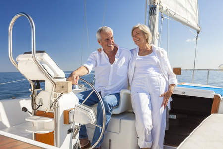 steering: A happy senior couple laughing having fun sailing at the wheel of a yacht or sail boat on a calm blue sea
