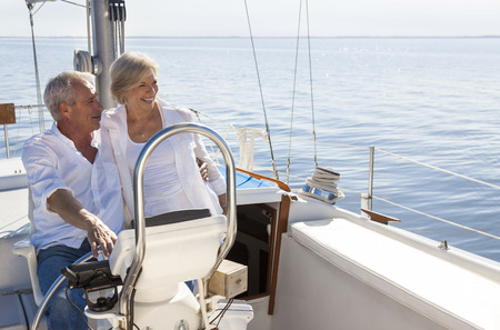 A happy senior couple sailing and sitting at the wheel of a sail boat on a calm blue sea Stock Photo