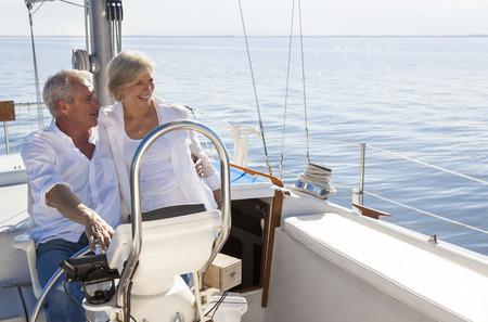 Een gelukkige senior paar zeilen en zitten aan het stuur van een zeilboot op een kalme blauwe zee