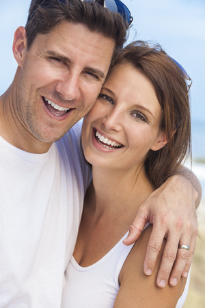 Portrait of a  man and woman romantic couple in white clothes embracing and laughing with oerfect smiles on a beach with bright clear blue sky Stock Photo