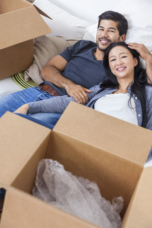 Asian Chinese couple laying back relaxing exhausted packing or unpacking boxes and moving into a new home. photo