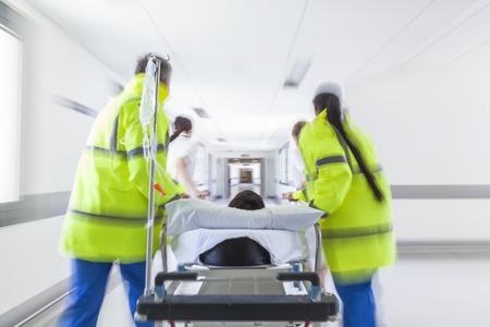 paciente en camilla: Una fotografía de movimiento borrosa de un paciente en camilla o camilla siendo empujado a la velocidad a través de un pasillo del hospital por los médicos y enfermeras a un accidente y la sala de emergencia Foto de archivo