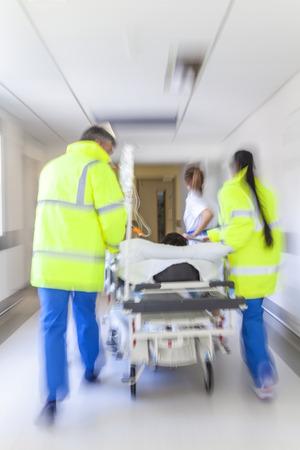 paciente en camilla: Una moción borrosa foto de un paciente en camilla o camilla de ser empujado a la velocidad a través de un pasillo del hospital por los médicos y enfermeras de la sala de emergencias