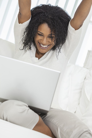 Beautiful African American woman happy and surprised successful celebration using her laptop computer.