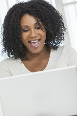 Beautiful African American woman open mouthed happy and surprised using her laptop computer. photo