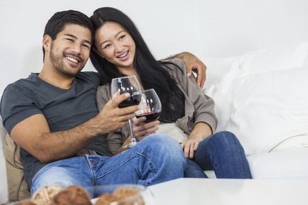 Asian Chinese romantic man woman couple drinking glass of red wine at home together