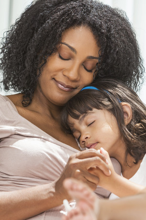 Portrait of a beautiful middle aged African American woman at home relaxing resting sleeping with her female child daughter Banco de Imagens