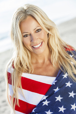 Beautiful young blond girl or young woman smiling wearing bikini and wrapped in American flag towel on a sunny beach