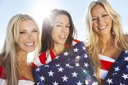 Three beautiful young women wearing bikinis, wrapped in American flags, smiling, laughing and having fun party on a sunny beach