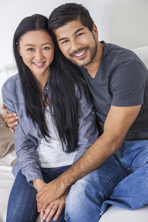 Asian Chinese man woman happy romantic couple relaxing together at home.