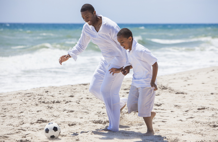 sunny beach: African American family of father and son, man & boy child, having fun playing football soccer in the sand on a sunny beach