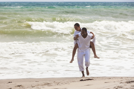 African American family of father and son, man & boy child, playingpiggy back and having fun in the sand and waves on a sunny beach