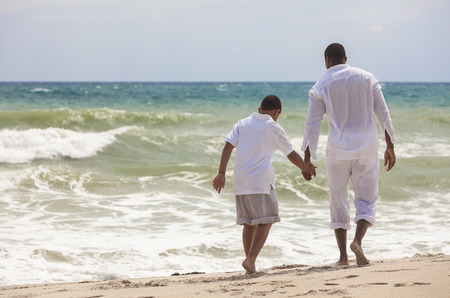 African American family of father and son, man & boy child, walking, holding hands and having fun in the sand and waves on a sunny beach