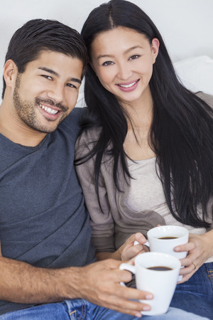 Asian Chinese couple relaxing at home drinking mugs or cups of tea or coffee.