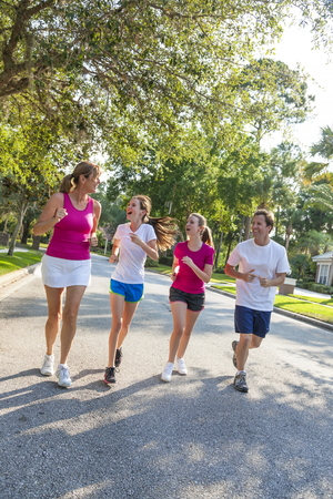 A fit happy and healthy family, man, woman, mother, father parents and two girl children road running and having fun outside together in summer sunshine photo