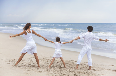 A happy family of mother, father and girl child walking holding hands and having fun in the sand on a sunny beach Banco de Imagens