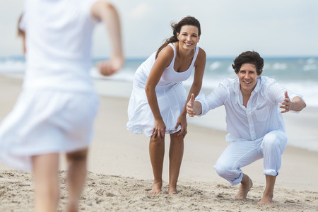 A happy family of mother, father and one child, a daughter, running and having fun in the sand of a sunny tropical beach