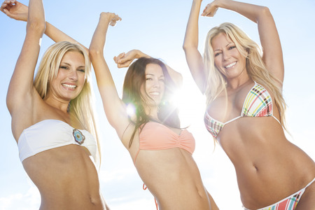 three friends: Three beautiful young women or girls in bikinis dancing backlit with sun lens flare on a sunny beach