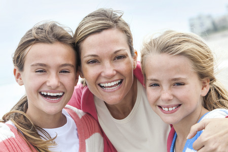 Happy woman mother and her female girl children having fun together laughing and smiling on vacation at a beach Stock Photo