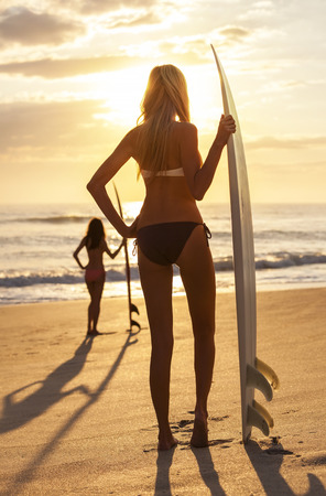 Rear view of two beautiful sexy young woman surfer girls in bikinis with surfboards on a beach at sunset or sunrise photo