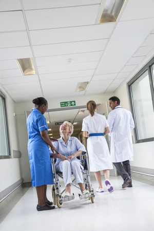 nhs: Senior female woman patient in wheelchair sitting in hospital corridor with African American female nurse and Asian doctor