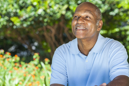 old man smiling: A happy senior African American man in his sixties outside smiling.