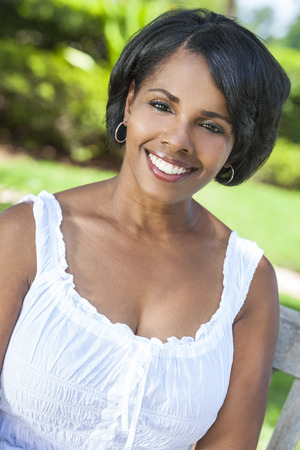 middle aged woman smiling: A beautiful happy middle aged African American woman relaxing and smiling outside