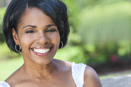 teeth smile: A beautiful happy middle aged African American woman relaxing and smiling outside