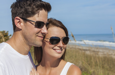 Portrait of a man and woman romantic couple in white clothes wearing sunglasses on a beach with bright clear blue sky