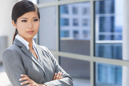 Outdoor portrait of a beautiful young Asian Chinese woman or businesswoman in smart business suit