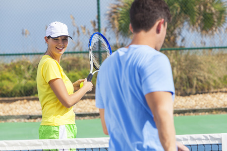 Young man and woman couple playing tennis or having tennis lesson