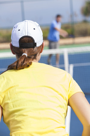 Rear view of young man and woman couple playing tennis or having tennis lesson photo