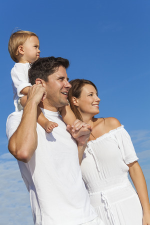 Portrait of a man and woman boy child couple family in white clothes happy and smiling on a beach with bright clear blue sky
