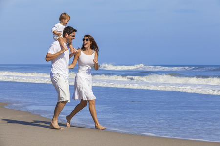Happy Man and woman boy child couple family in white clothes walking playing on a deserted empty tropical beach with bright clear blue sky Stockfoto