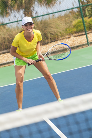 Beautiful happy girl or young woman laughing smiling and playing tennis photo