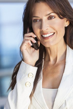 thirties: Outdoor portrait of a beautiful happy brunette woman or businesswoman in her thirties talking on her cell phone