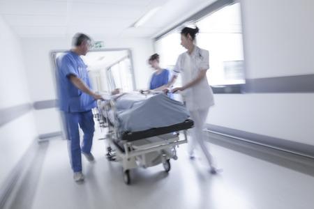 Une photographie de mouvement floue d'une patiente de haut niveau sur civière ou civière poussé à la vitesse à travers un couloir de l'hôpital par les médecins et les infirmières à une salle d'urgence