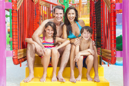 A happy family of mother, father and children, son and daughter, having fun on vacation at a water park Banco de Imagens