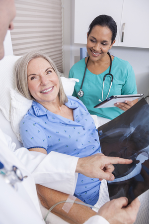 A happy senior female woman elderly patient in bed looking at X-ray of a hip replacement operation with male doctor and Hispanic nurse